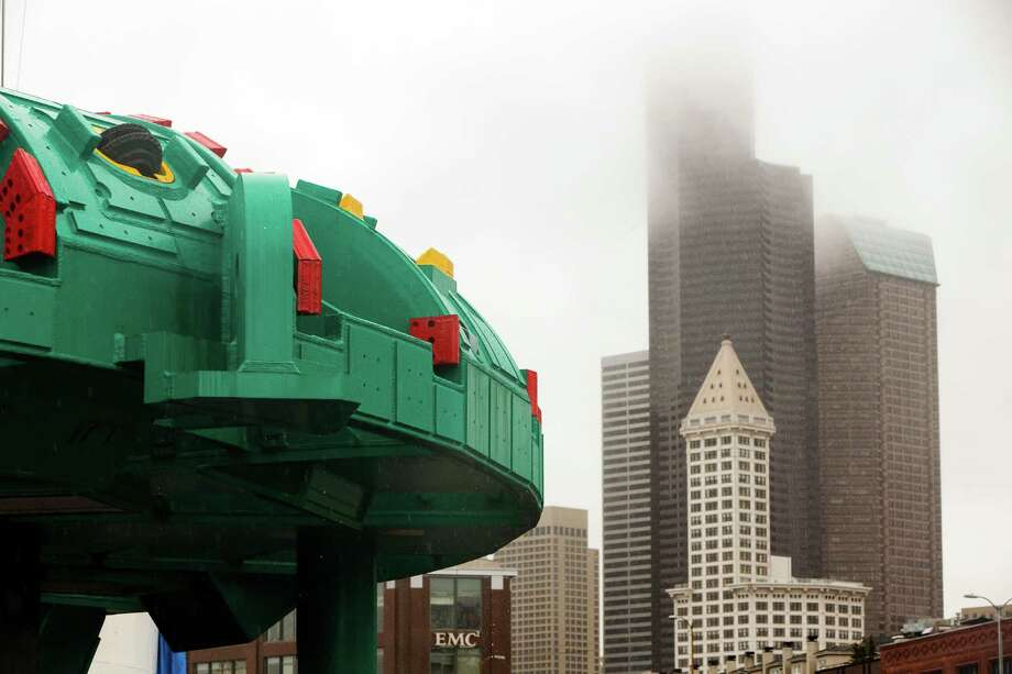 Colorful bits of the Bertha SR 99 tunneling machine stand out against a gray sky during a guided tour of the Alaskan Way Viaduct replacement program's progress at the site of the drill's launch point Friday west of CenturyLink Field in Seattle. The 41 pieces that make up the drill have been unloaded from the Jumbo Fairpartner and are now stored around the site. Later this month, crews will begin lowering the pieces into the launch pit for reassembly and testing. Photo: JORDAN STEAD, SEATTLEPI.COM / SEATTLEPI.COM