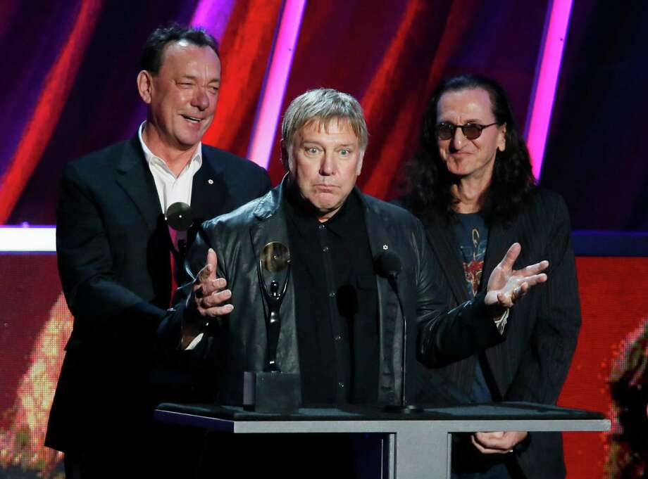 Alex Lifeson, center, Neil Peart, left, and Geddy Lee, of Rush accept their band's induction into the Rock and Roll Hall of Fame during the Rock and Roll Hall of Fame Induction Ceremony at the Nokia Theatre on Thursday, April 18, 2013 in Los Angeles. (Photo by Danny Moloshok/Invision/AP) Photo: Danny Moloshok