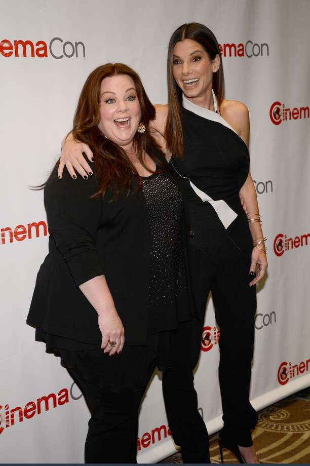 """Actresses Melissa McCarthy (L) and Sandra Bullock arrive at a Twentieth Century Fox presentation to promote the upcoming film \""""The Heat\"""" at Caesars Palace during CinemaCon, the official convention of the National Association of Theatre Owners, on April 18, 2013 in Las Vegas, Nevada."""