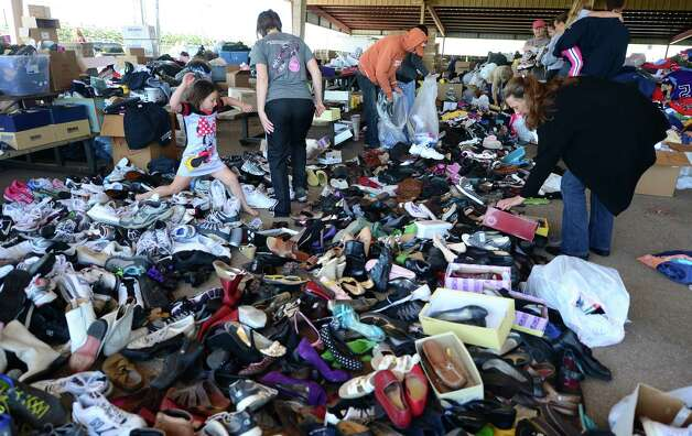 A woman rummages through a hugh pile of shoes at a distribution center where supplies like water and clothing, including medical supplies, are being dropped off or picked up as needed, in West, Texas, on April 19 2013, two days after a deadly fertilizer plant blast occured.  While rescuers in Texas were set to return to the rubble in their continuing search for survivors after the massive blast killed as many as 15 people and destroyed dozens of homes, all roads leading to the area of destruction have been closed off and manned by various state authorities controlling the entry and exit of vehicles and people.      AFP PHOTO/Frederic J. BROWNFREDERIC J. BROWN/AFP/Getty Images Photo: FREDERIC J. BROWN, AFP/Getty Images / AFP
