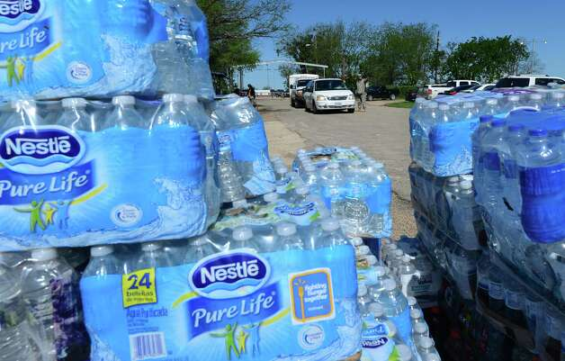 Stacks of 'Pure Life' water sit on the roadside as vehicles are directed to a distribution center where supplies like water and clothing, includin