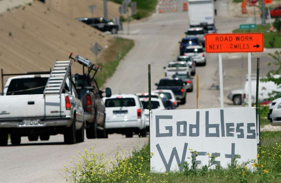 "A ""God Bless West"" sign in West, Texas, Friday April 19, 2013. The bodies of 12 people have been recovered after an enormous Texas fertilizer plant explosion that demolished surrounding neighborhoods for blocks and left about 200 other people injured, authorities said Friday. (AP Photo/Mike Fuentes) Photo: Mike Fuentes, Associated Press / FR103746 AP"