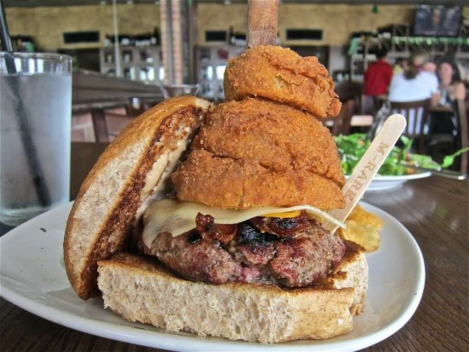 The Union Kitchen's namesake burger is stacked high with onion rings and impaled by a butcher knife, 12538 Memorial in Houston. Photo: Alison Cook