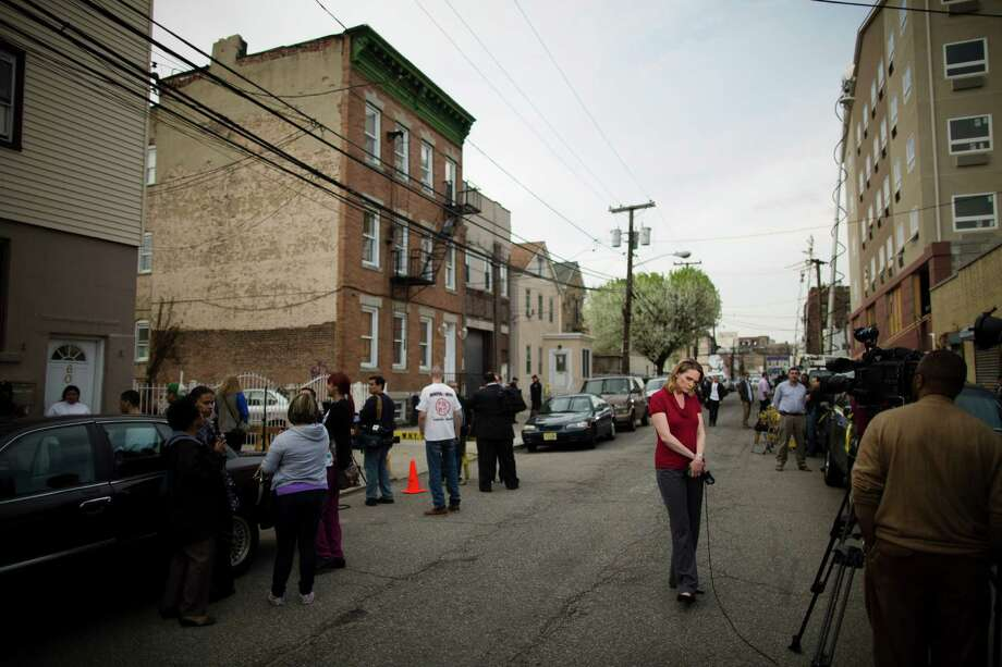 A news reporter waits for her cue as police guard the apartment building where the sister of the Boston marathon bombing suspects is believed to live, Friday, April 19, 2013, in West New York, N.J. Federal investigators had removed items from the house earlier in the day, although there is no indication that the sister was involved in the bombing. (AP Photo/John Minchillo) Photo: Wire