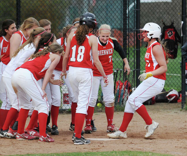 At right, Alison Kach of Greenwich is greeted by her teammates as she touches home plate after hitti