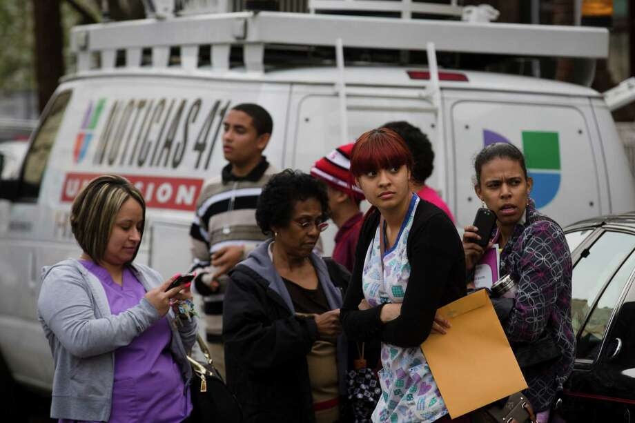 Bystanders look on as police guard the apartment building where the sister of the Boston marathon bombing suspects is believed to live, Friday, April 19, 2013, in West New York, N.J. Federal investigators had removed items from the house earlier in the day, although there is no indication that the sister was involved in the bombing. (AP Photo/John Minchillo) Photo: John Minchillo, FRE / FR170537 AP
