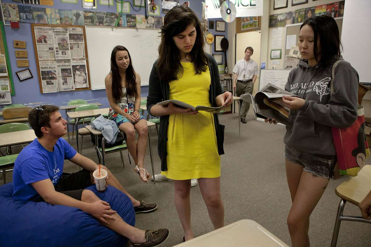 Palo Alto High school students including columnist Will Queen (left), Diana Connolly (sitting on desk/ did the editorial and intographic on the story), editors-in-chief Ana Carano (middle, wearing yellow) and Evelyn Wang (right, in shorts) gather in the classroom during lunch in Palo Alto, California, on Friday, April 19, 2013. The students did a recent cover story on sexual assault among teens.