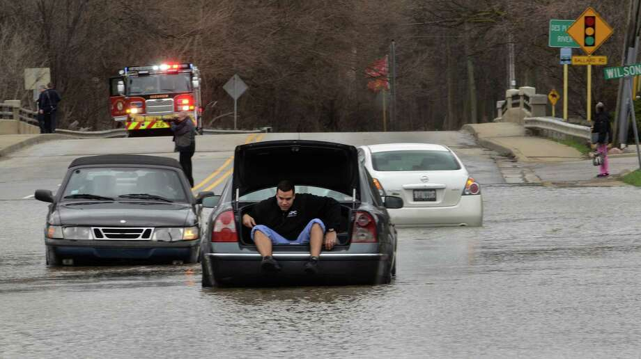 Efrain Baez crawls out the trunk of his car after getting stuck in a flooded intersection Des Plaines from flooding of the Des Plaines River on Friday. Photo: Bob Chwedyk, MBI / Daily Herald