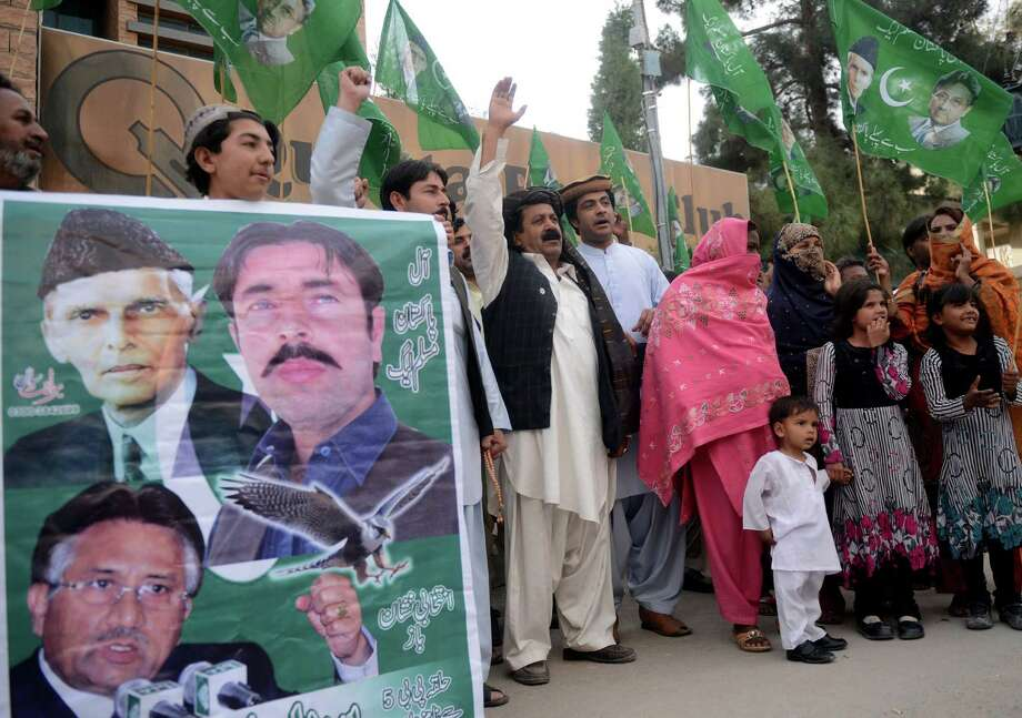 Supporters of former Pakistani military ruler Pervez Musharraf carry party flags during a pro-Musharraf rally on Friday in Quetta.  Musharraf was moved into police custody after being arrested on Friday. Photo: ASIF HASSAN, Stringer / AFP