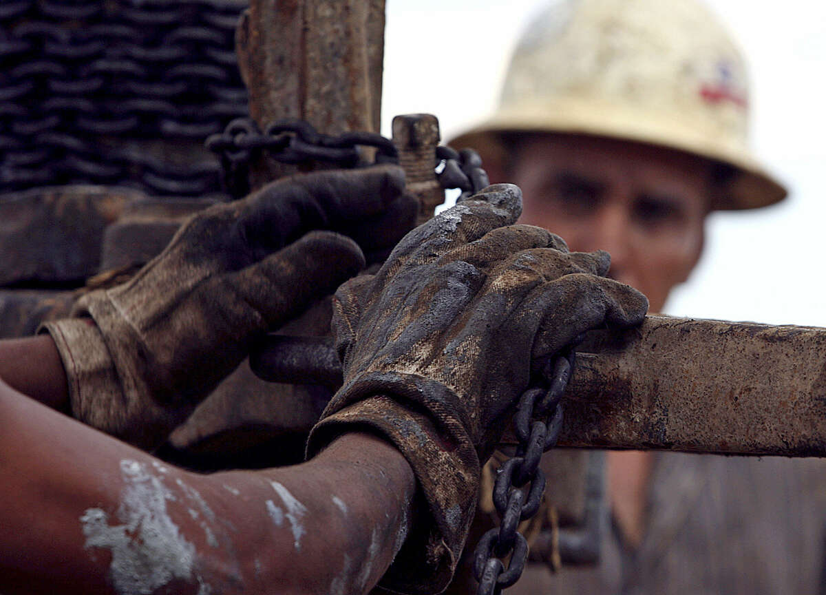 """Workers with National Oil help insert a metal pipe near Big Lake in 2006. The Obama administration says the president's budget would save $39 billion over the next 10 years by eliminating """"fossil fuel tax preferences"""" geared toward oil, gas and coal."""