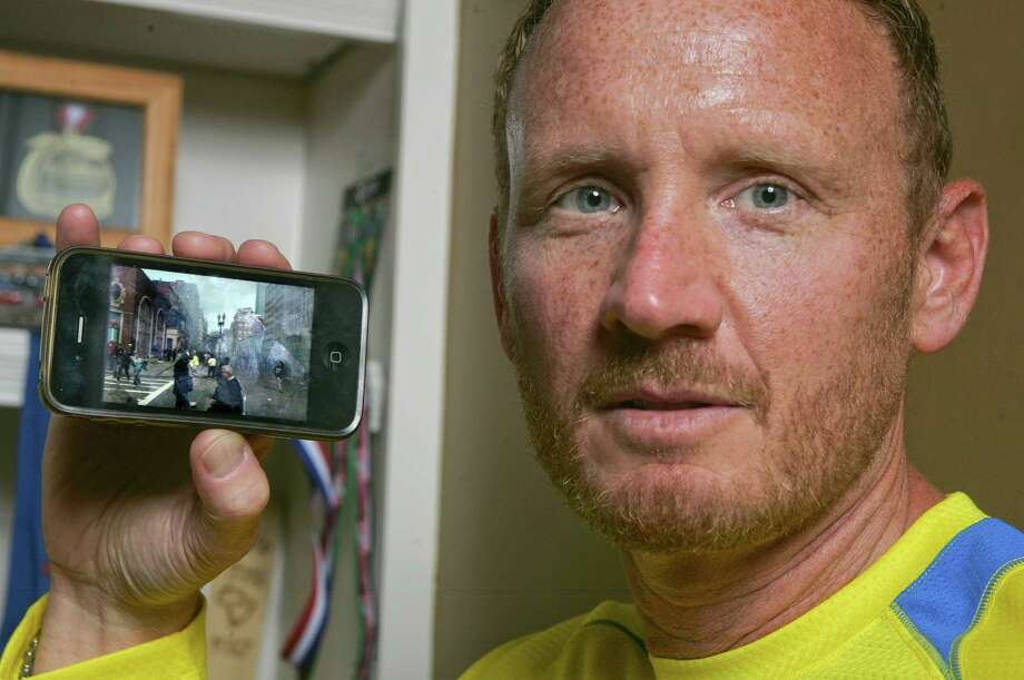 David Green holds up his iPhone with a photo on it he took after the Boston Marathon bombing Friday, April 19, 2013, at his home in Jacksonville, Fla. Seconds after the Boston Marathon bombs exploded, Green pulled out his smartphone and took the photo of the chaos developing a couple hundred yards in front of him -- the smoke, the people running in panic. The Jacksonville businessman then put his phone back in this pocket and went to help the injured. It wasn't until Thursday that Green realized what he had – a picture of suspect Dzhokhar A. Tsarnaev, distinctive in his backward white baseball cap, walking away from the scene. (AP Photo/Phil Sears) Photo: Phil Sears, FRE / FR170567 AP