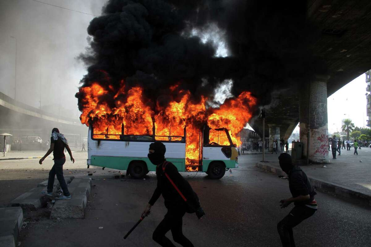 Egyptian protesters in Cairo clash near a burning bus belonging to Muslim Brotherhood supporters.