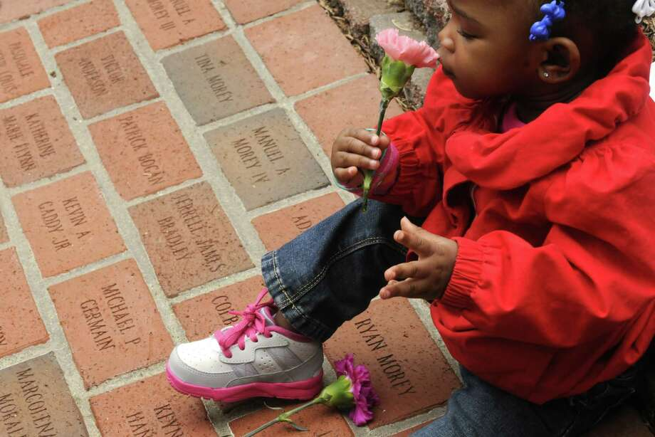 One-year-old Dmani Martin of Albany takes time to smell a carnation as she and her family visit the memorial brick for her uncle Jahod Crumble during the New York State Crime Victims Memorial on Friday April 19, 2013 in Albany, N.Y. (Michael P. Farrell/Times Union) Photo: Michael P. Farrell