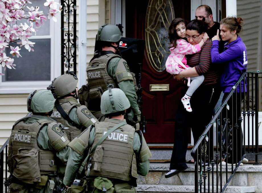 A woman carries a girl from their home as a SWAT team searches for a suspect in the Boston Marathon bombings on Friday in Watertown, Mass. After a long night of violence, one of the suspects was killed in a shootout with law enforcement and the other arrested. Photo: Charles Krupa, STF / AP