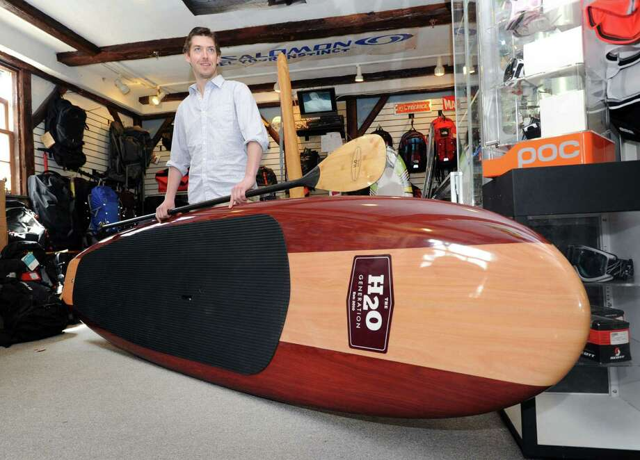 Cory Bixler, a manager at the Outdoor Traders store, displays a paddle board at the store in Greenwich, Friday, April 19, 2013. Bixler said the board sells for $900 and is used for stand up paddle boarding, a water sport that is gaining popularity. Photo: Bob Luckey / Greenwich Time