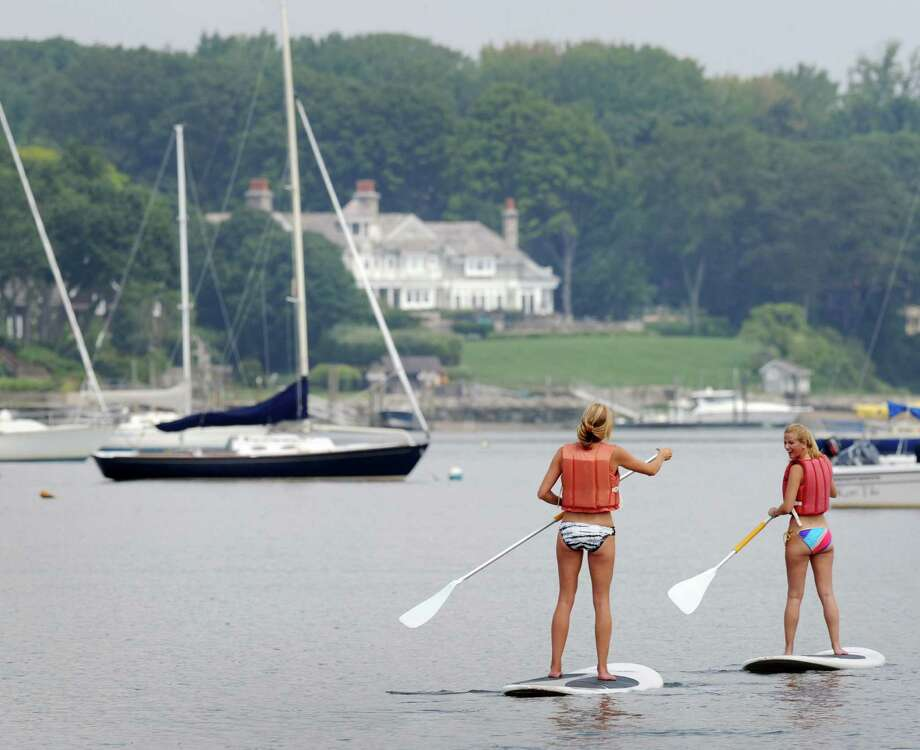 At left, Kim Heaney of Michigan, and friend, Christine Ridenour of Greenwich, paddleboard in Greenwich Cove, Saturday, Aug. 11, 2012. Photo: Bob Luckey / Greenwich Time