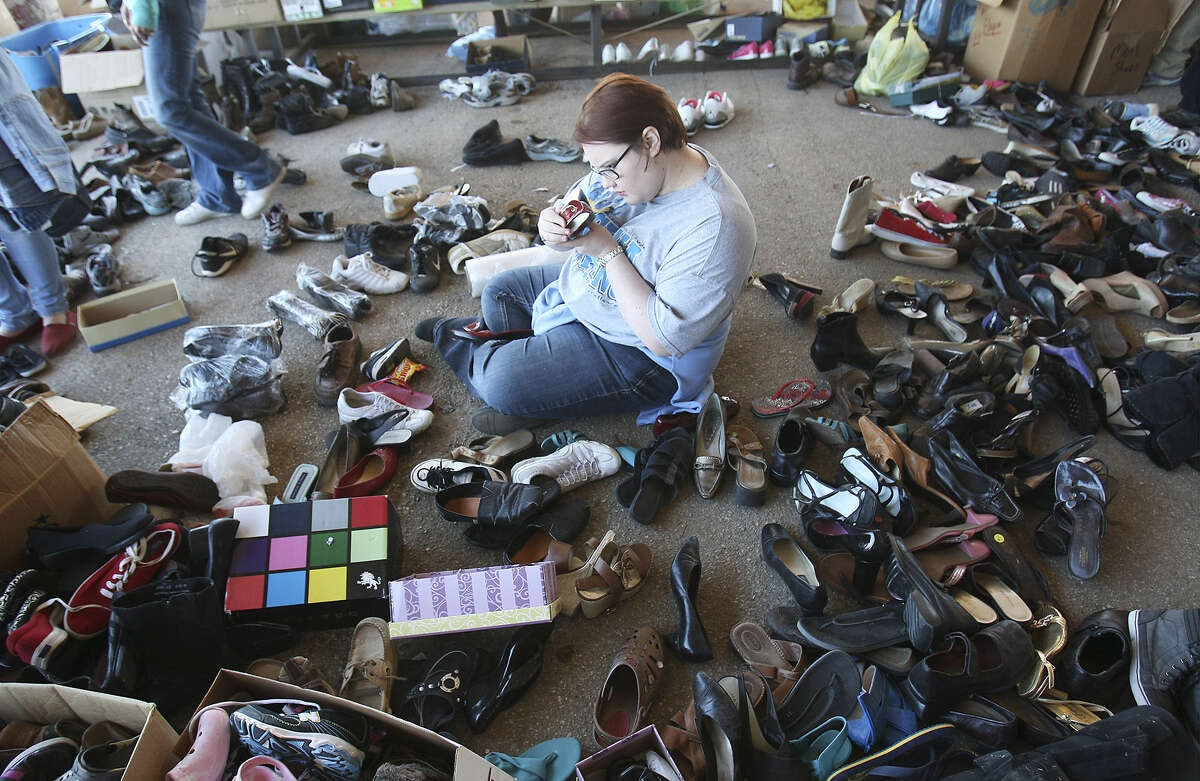 Danae Benton of China Springs, near Houston, sorts shoes that were brought to the Westfest pavilion, which was quickly turned into a distribution center for the community.
