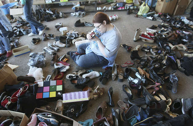 Danae Benton of China Springs, near Houston, sorts shoes that were brought to the Westfest pavilion, which was quickly turned into a distribution center for the community. Photo: Kin Man Hui / San Antonio Express-News