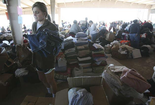 Volunteer Alissa Dawson, a student at Baylor University, sorts jeans. The pavilion was nearly empty Friday morning. Photo: Kin Man Hui / San Antonio Express-News