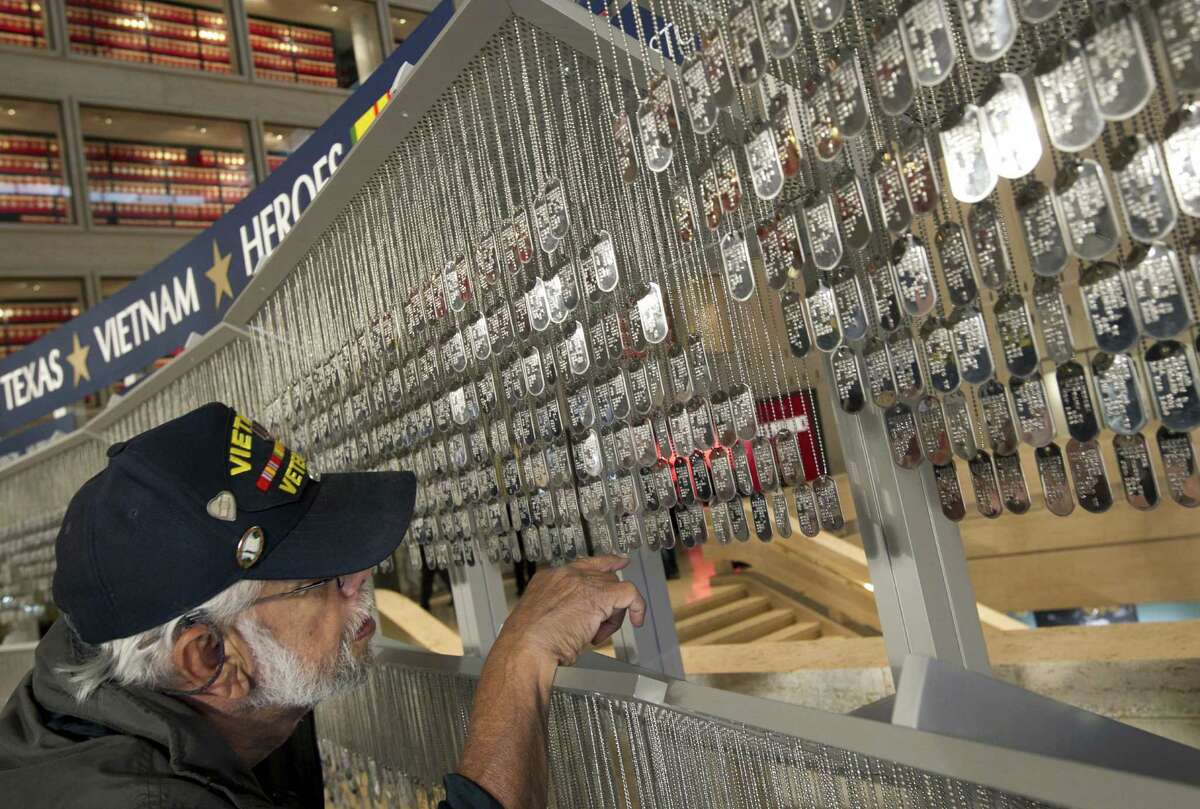 Vietnam veteran Hector Avila looks for the dog tags with the names of his childhood friends at the Texas Vietnam Heroes exhibit at the Lyndon B. Johnson Presidential Library in Austin, Texas, on Sunday March 24, 2013. The exhibit features a dog tag for each of the Texans who died in the Vietnam War. The exhibit is in advance of Monday's groundbreaking ceremony for the Texas Capitol Vietnam Veterans Monument. (AP Photo/Austin American-Statesman, Jay Janner)