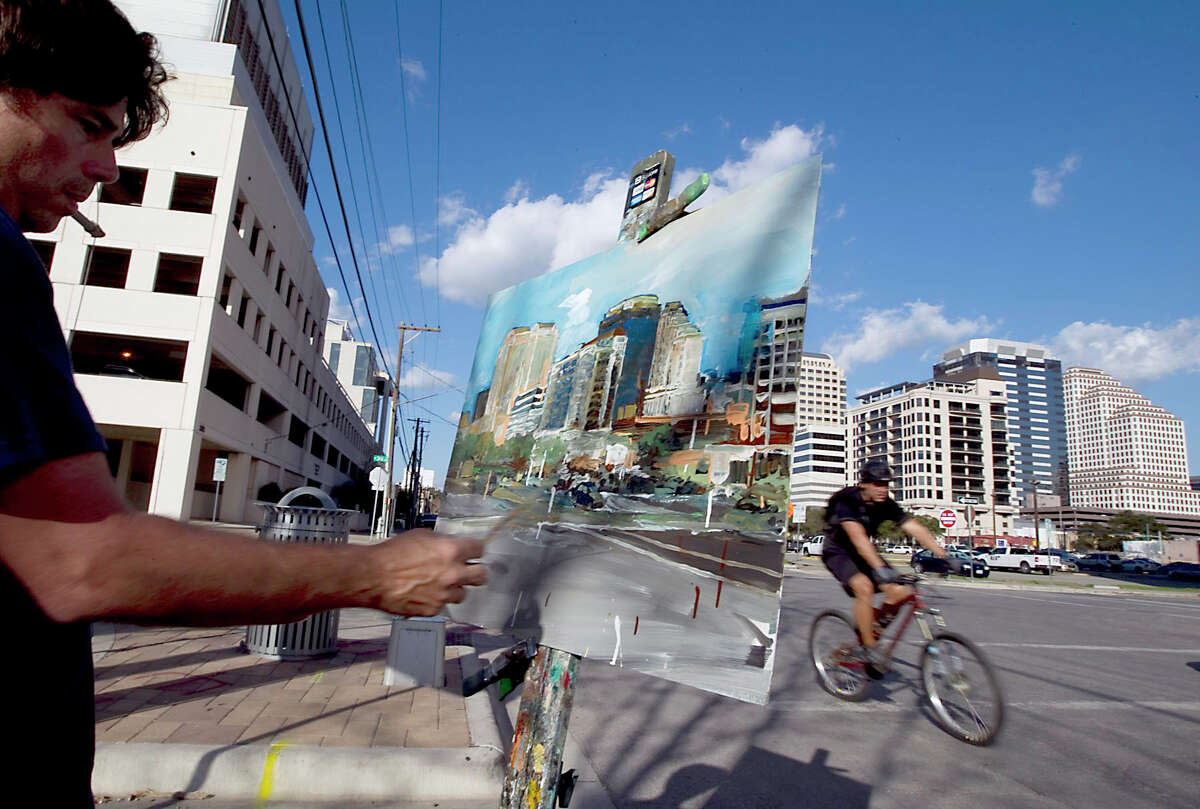 Artist Chris Chappell enjoys the weather as he paints the skyline at the corner of 3rd Street and San Antonio in Austin, Texas on Wednesday, February 1, 2012. (AP Photo/Austin American-Statesman, Rodolfo Gonzalez ) MAGS OUT; NO SALES; TV OUT; INTERNET OUT; AP MEMBERS ONLY