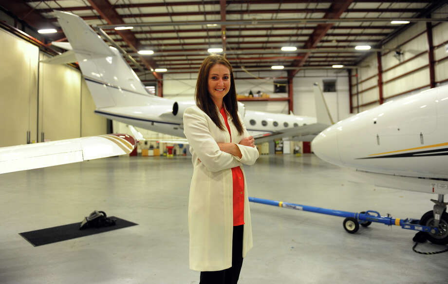 MacKenzie Stuart, a Washington, Conn. native, poses at the Oxford Airport where she worked for a year, in Oxford, Conn. on Friday April 12, 2013. Stuart is both a commercial pilot and a financial adviser, who now lives in Boston. Photo: Christian Abraham / Connecticut Post