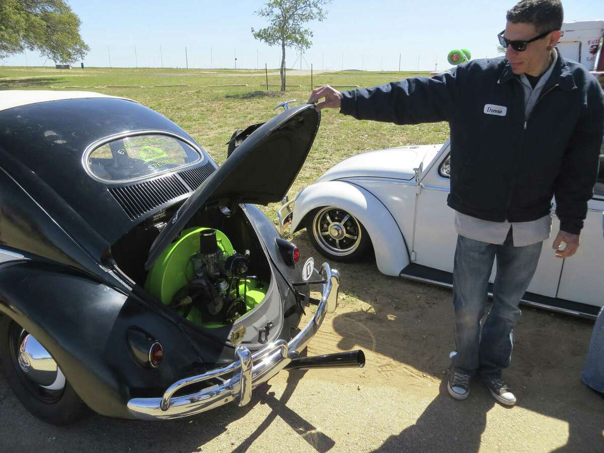"""Donnie Kellar, who bought his first Volkswagen at age 8, shows off the restored engine in his 1956 Beetle, which he's selling for $9,000. """"Every year I bring a different car to sell"""" in Fredericksburg, he said."""