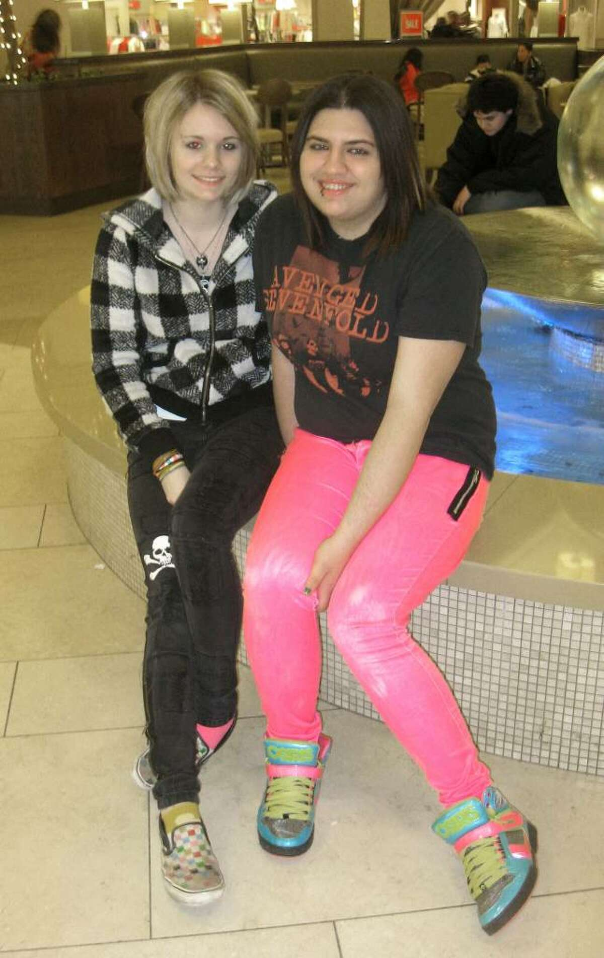 (from left) Sam Bucur, 18, and Sarah Steiner, 18, both of Newtown, sit in on the fountain at the Danbury Fair Mall Tuesday night. They come to the mall to go shopping and eat food.