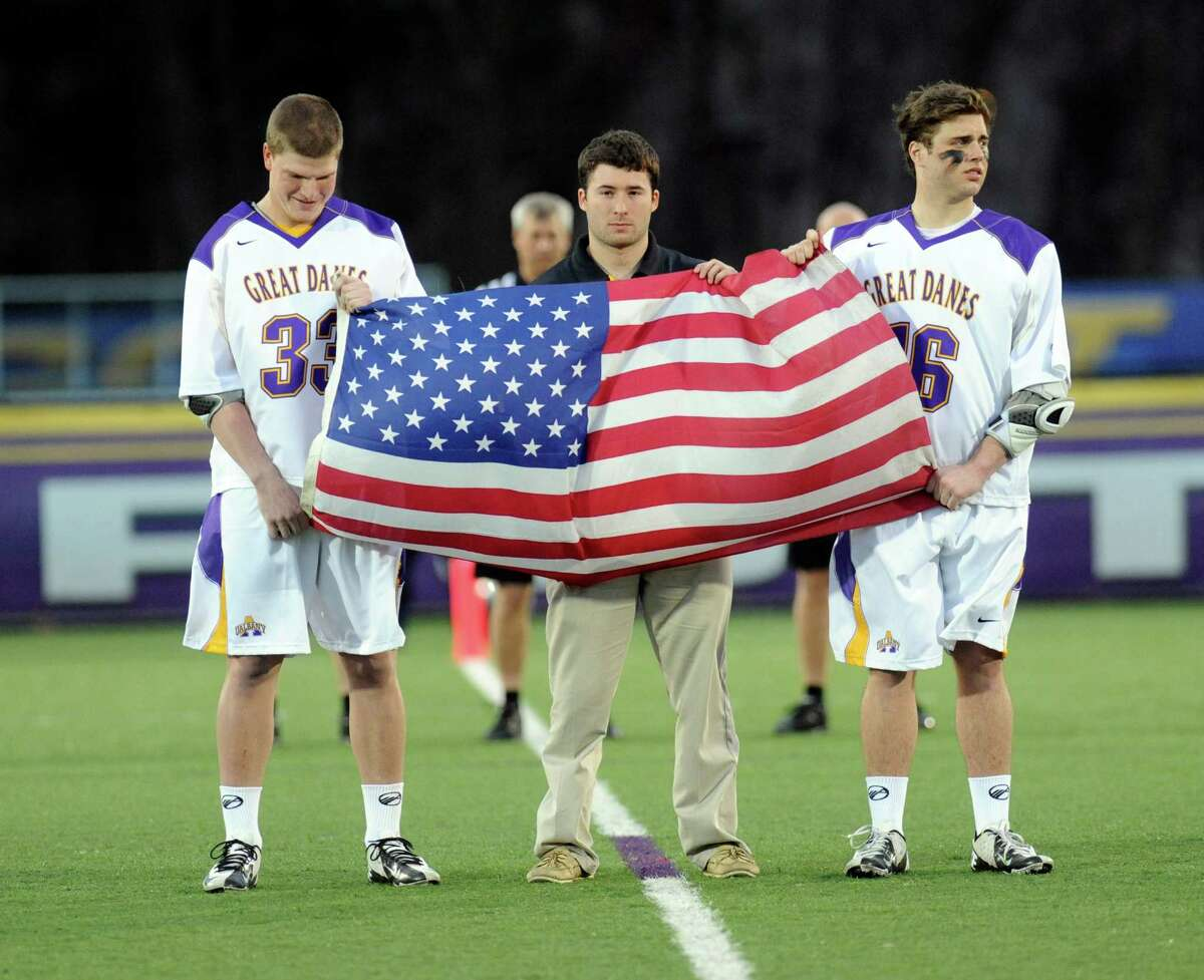UAlbany's Sam Leahy ,left, and teammate Will Stenbeck ,right, with UMBC's Connor Gordon ,center, all from the state of Massachusetts hold an American Flag during a moment of silence for those who died in the Boston bombing prior to an NCCA Lacrosse game in Albany, N.Y., Friday, April 19, 2013. (Hans Pennink / Special to the Times Union)