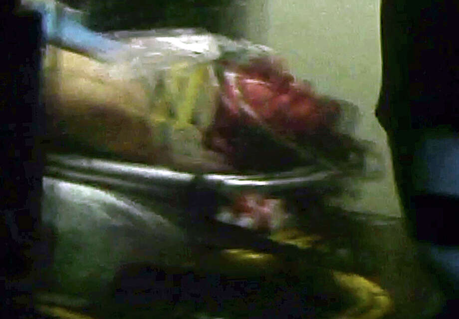 ALTERNATE CROP - This still frame from video shows Boston Marathon bombing suspect Dzhokhar Tsarnaev visible through an ambulance after he was captured in Watertown, Mass., Friday, April 19, 2013.A 19-year-old college student wanted in the Boston Marathon bombings was taken into custody Friday evening after a manhunt that left the city virtually paralyzed and his older brother and accomplice dead. (AP Photo/Robert Ray) Photo: Robert Ray, STF / AP