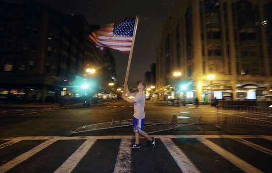 Joseph Eli Libby, 20, of Boston, carries a flag near a makeshift memorial on Boylston Street, near the finish line of the Boston Marathon, Friday, April 19, 2013, in Boston. Boston Marathon bombing suspect Dzhokhar Tsarnaev was captured in Watertown, Mass. The 19-year-old college student wanted in the bombings was taken into custody Friday evening after a manhunt that left the city virtually paralyzed and his older brother and accomplice dead. (AP Photo/Julio Cortez) Photo: Julio Cortez, Wire / AP2013