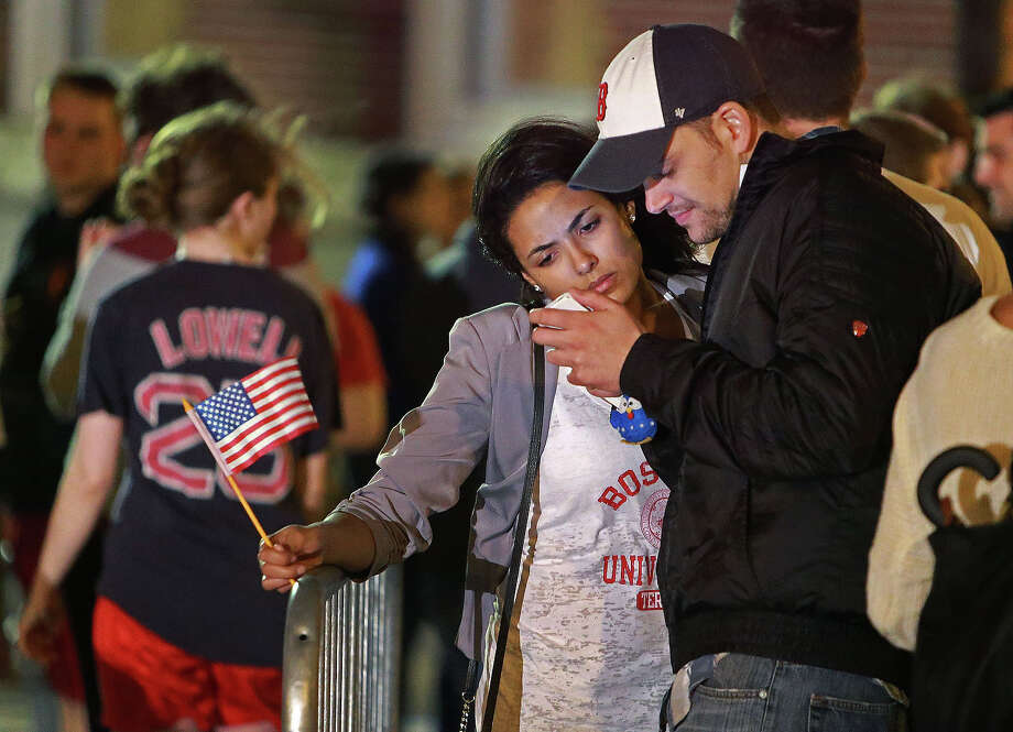 After the second suspect was captured, people came to the barricades at the corner of Boylston and Hereford Streets near the Marathon Finish line to celebrate and reflect. A couple looks at a device as the woman carries an American flag. Photo: Boston Globe, Wire / 2013 - The Boston Globe