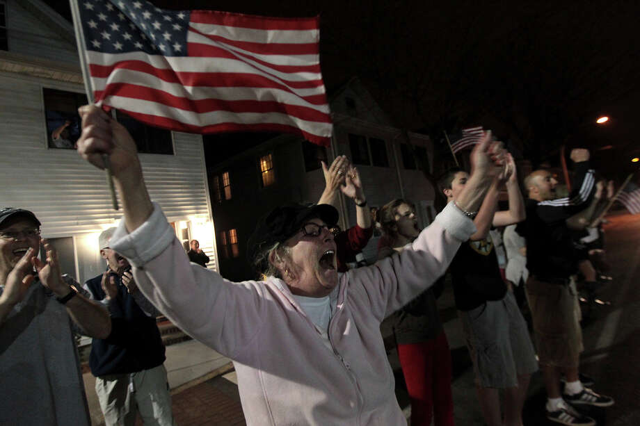 On Arsenal Street, Louise Hunter and others cheer on police on leaving the scene. After an intense manhunt and two-hour standoff in Watertown, law enforcement took a person into custody believed to be related to the Boston Marathon bombings. Photo: Boston Globe, Wire / 2013 - The Boston Globe