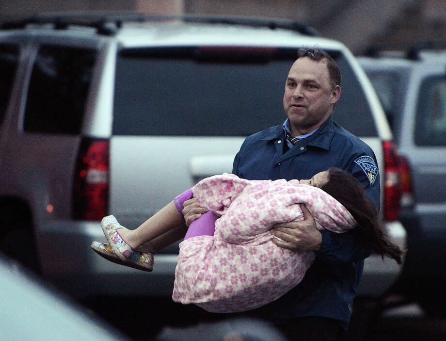An officer carries a child away from an area where a suspect is hiding on Franklin St., on April 19, 2013 in Watertown, Massachusetts. After a car chase and shoot out with police, one suspect in the Boston Marathon bombing, Tamerlan Tsarnaev, 26, was shot and killed by police early morning April 19, and a manhunt is underway for his brother and second suspect, 19-year-old Dzhokhar A. Tsarnaev. The two men are suspects in the bombings at the Boston Marathon on April 15, that killed three people and wounded at least 170. Photo: Darren McCollester, Wire / 2013 Getty Images
