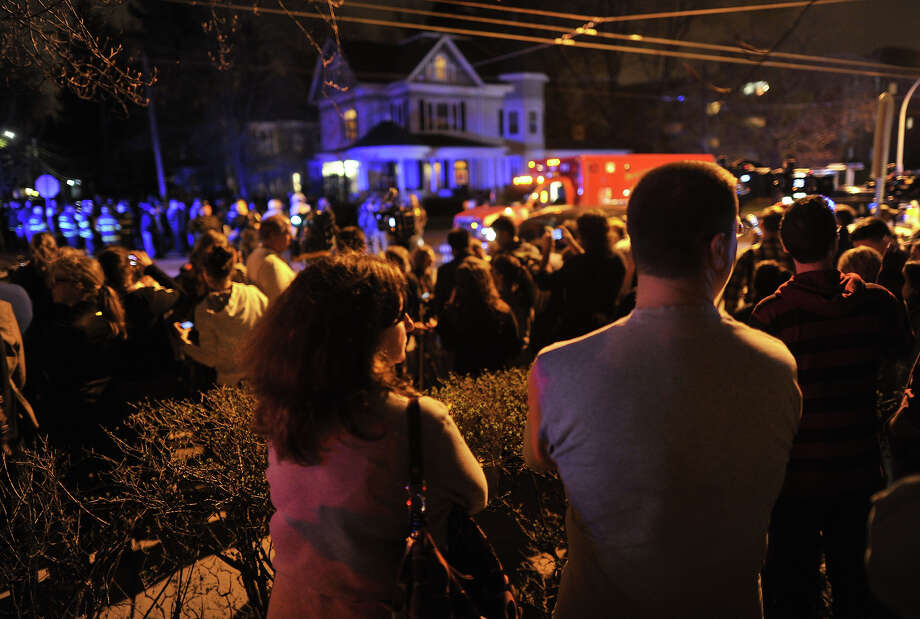 Residents await the capture of  the second of two suspects wanted in the Boston Marathon bombings April 19, 2013 in Watertown, Massachusetts. Thousands of heavily armed police staged an intense manhunt for a Chechen teenager suspected in the Boston marathon bombings with his brother, who was killed in a shootout. Dzhokhar Tsarnaev, 19, defied the massive force after his 26-year-old brother Tamerlan was shot and suffered critical injuries from explosives believed to have been strapped to his body. AFP PHOTO / TIMOTHY A. CLARY        (Photo credit should read TIMOTHY A. CLARY/AFP/Getty Images) Photo: TIMOTHY A. CLARY, Wire / 2013 AFP