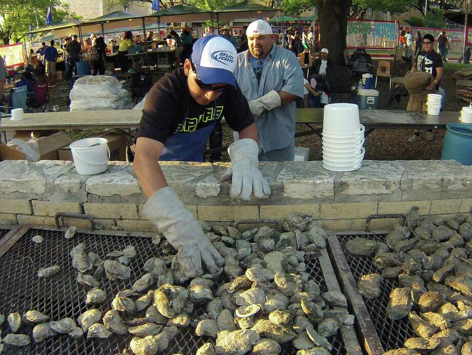 Rudy Herrera and Rafael Alarcon prepare oysters during Fiesta Oyster Bake 2013 at St. Mary's University on Friday, April 19, 2013. The event funds the university's student scholarships and university and alumni programs. Photo: Billy Calzada, Express-News / San Antonio Express-News
