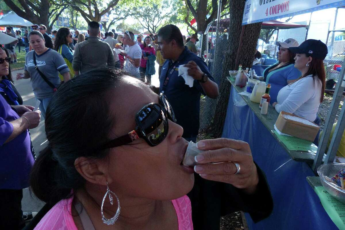 Sonia Vest tries an oyster shot during Fiesta Oyster Bake 2013 at St. Mary's University on Friday, April 19, 2013.
