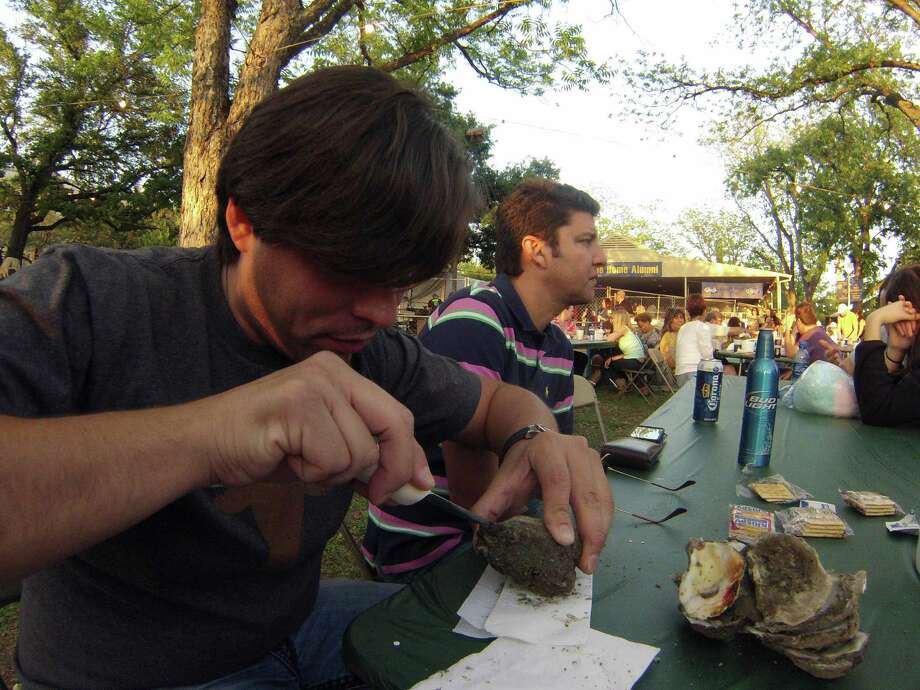 Javier Gil shucks an oyster during Fiesta Oyster Bake 2013 at St. Mary's University on Friday, April 19, 2013. The event funds the university's student scholarships and university and alumni programs. Photo: Billy Calzada, Express-News / San Antonio Express-News