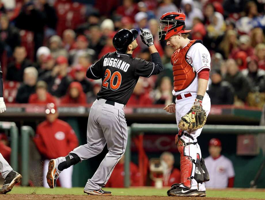 Marlins outfielder Justin Ruggiano, left, was the man of the hour after delivering a ninth-inning home run to sink Ryan Hanigan and the Reds. Photo: Andy Lyons, Staff / 2013 Getty Images