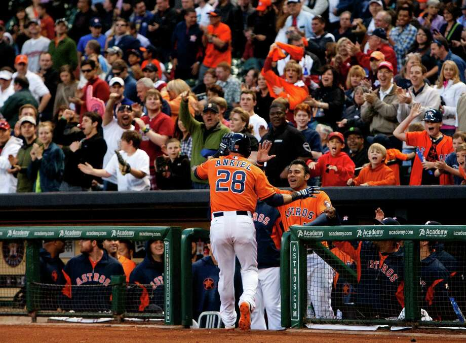 With plenty of happy fans providing a backdrop, Astros right fielder Rick Ankiel works the receiving line in the Astros' dugout after hitting a home run off Indians starter Brett Myers in the second inning. Photo: Cody Duty, Staff / © 2013 Houston Chronicle