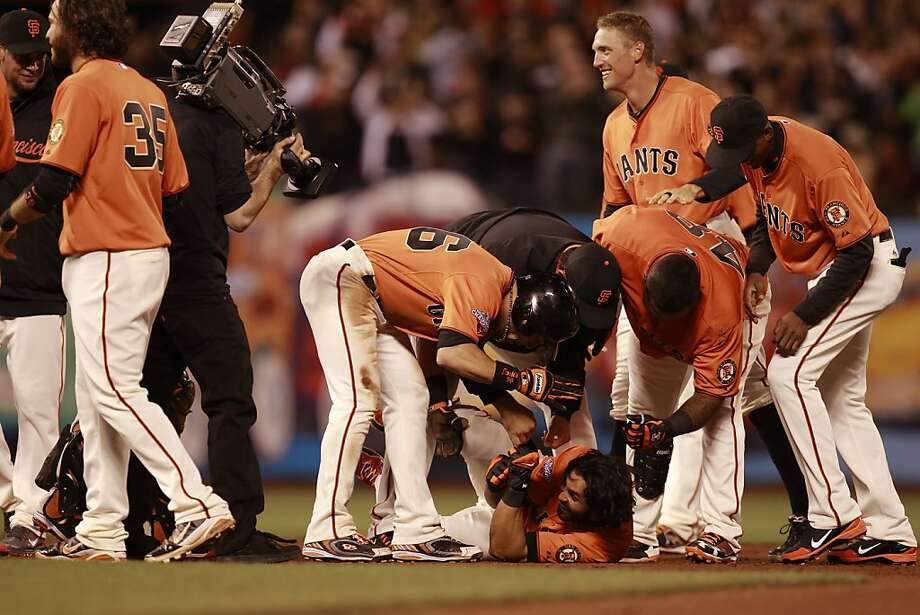 It's a down to earth celebration of the winning run for Angel Pagan (bottom center), who drove it in. Photo: Michael Macor, The Chronicle
