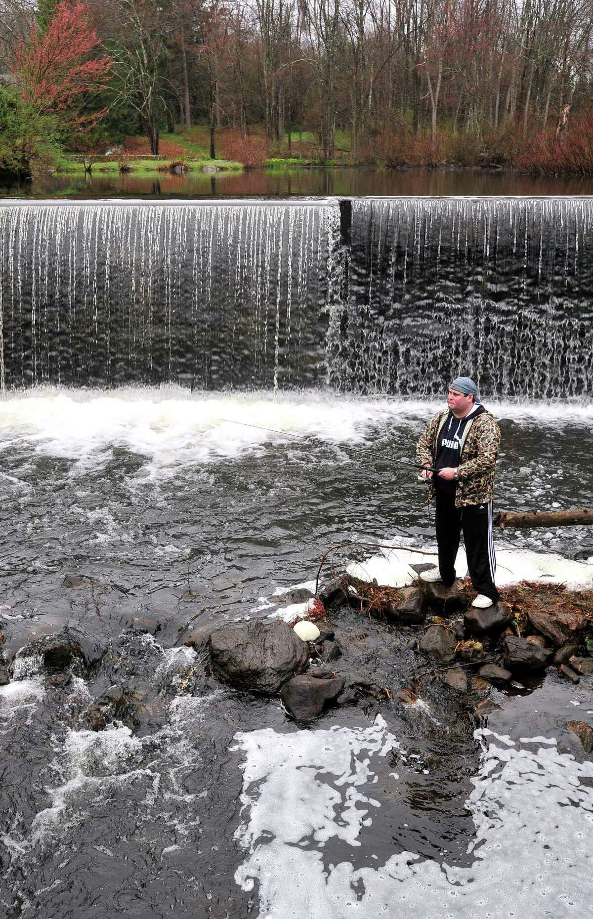 Paul Tilinek, of New Milford, fishes on the opening day of fishing season along the Saugatuck River in Redding, Conn. Saturday, April 20, 2013.