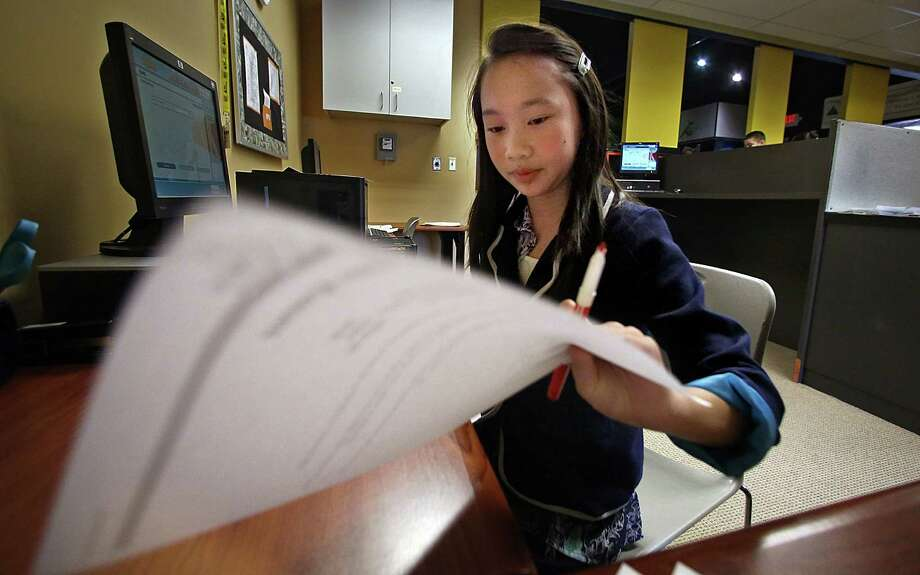 Greenleaf Elementary School student and bank CEO Nulia Nguyen, 10, examines documents in BizTown, a simulated city at Junior Achievement in Maplewood, Minnesota, where fourth- and fifth-graders spend a day learning to run a business, work for a boss, write a check, pay taxes and do payroll. (Jim Gehrz/Minneapolis Star Tribune/MCT) Photo: Jim Gehrz / Minneapolis Star Tribune