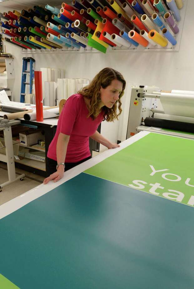 Graphic designer Moira Driscoll looks over some of the output in the printing department of Creatacor Thursday, April 11, 2013, in Clifton Park, N.Y.    (Skip Dickstein/Times Union) Photo: SKIP DICKSTEIN / 10021937A
