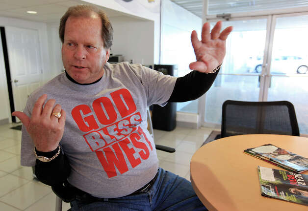 """Greg May Chevrolet used car manager Ronnie Owens wears a """"God Bless West"""" t-shirt ,Friday April 19, 2013, that is being sold at the dealership after an explosion at a fertilizer plant that occurred Wednesday evening in West, Tx. The money raised from the t-shirt is benefitting the West Independent School District. Photo: Edward A. Ornelas, San Antonio Express-News / © 2013 San Antonio Express-News"""