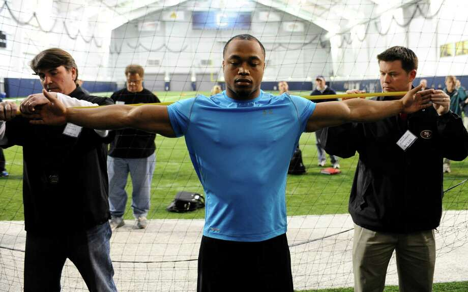 UConn defensive end Trevardo Williams, right, has his arm measured by Panthers scout Robert Haines, left, and 49ers Scout Chip Flanagan, right, during pro day in Storrs, Conn., Wednesday, March 27, 2013.  (AP Photo/Jessica Hill) Photo: Jessica Hill, Associated Press / FR125654 AP