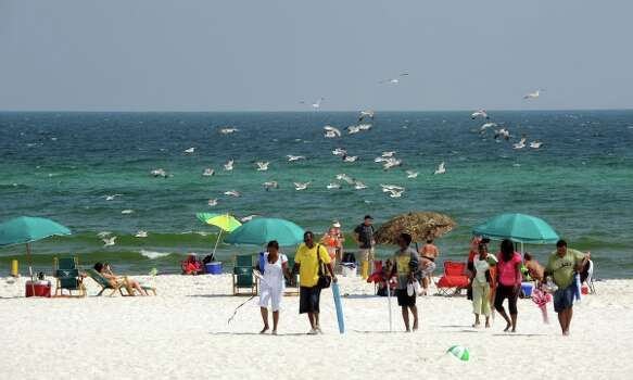 FILE-  This Sunday, July 11, 2010 file photo shows beach goers at Pensacola Beach in Pensacola, Fla. Efforts to cap the oil well are under way. But even if they are successful at stopping the gusher, the tourist-dependent Florida Panhandle now faces the hurdle of luring visitors back to a coastline that still could see tar balls wash ashore. Photo: AP