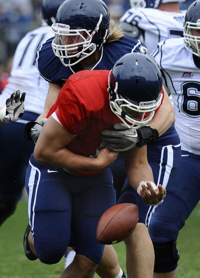 Connecticut quarterback Scott McCummings fumbles the ball when hit by Connecticut's Andreas Knappe during UConn's Blue-White spring NCAA college football game at Rentschler Field in East Hartford, Conn., Saturday, April 20, 2013. (AP Photo/Jessica Hill)