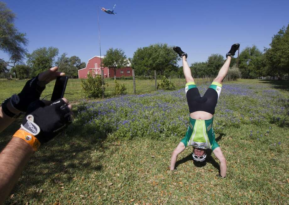 Drew Uruski has his picture taken by Gerard Guderian as he attempts a hand stand during a stop along FM 529 towards Bellville on route to Austin during the BP MS 150 on Saturday, April 20, 2013, in Houston.