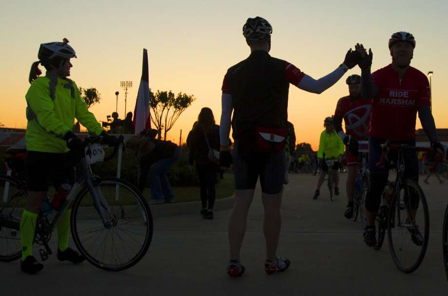 Cyclists give each other high fives as they begin their journey from Tully stadium, one of three starting points, to Austin during the BP MS 150 on Saturday, April 20, 2013, in Houston.